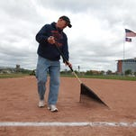 In this 2013 photo, Jerry Bagierek rakes the field as others from the Navin Field Grounds Crew cleans up the old Tiger Stadium.