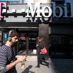 FILE - In this Sept. 12, 2012 file photo, A man uses a cellphone as he passes a T-Mobile store on Sept. 12, 2012, in New York.