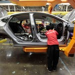 Assembly line workers build a 2015 Chrysler 200 automobile at the Sterling Heights Assembly Plant in Sterling Heights, Mich.