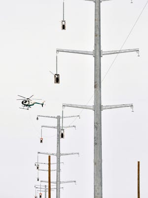 An AIR 2 helicopter strings power transmission lines through a series of about 20 electrical towers for the CapX 2020 project in 2014 along Stearns County Road 2 between St. Joseph and Cold Spring.