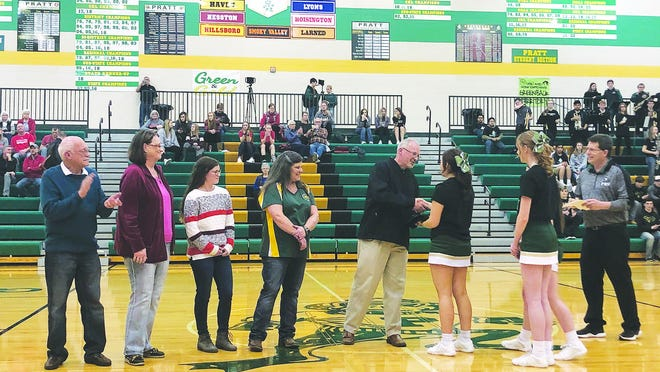 Command Sergeant Major David Schmidt is welcomed back to Pratt earlier this month by Greenback cheerleaders Halley Perez, Katherine Shanline and Liz Voss during halftime of a PHSbasketball game. Schmidt served as a medical care coordinator in Kuwait. His wife Carol, daughter Morgan, and parents  (not pictured) were also part of the welcome home ceremony. courtesy photo