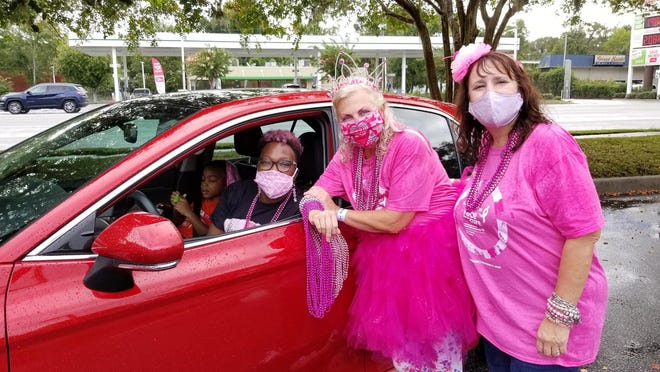 Felicia Thompson, in car, and volunteers, Elizabeth Myers and Patti Clark all are breast cancer survivors who participated in the Survivor Car Parade on Saturday.