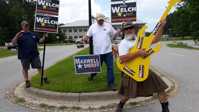 From left, Monty Ranisate, candidate for sheriff Keith Welch, and guitar twirler Kevin Manning were in front of the Bryan County Administration Building in Richmond Hill on election day. Mark Crowe and Al Hagan each won their primary election races June 9 to run for the Sheriff's post in November.