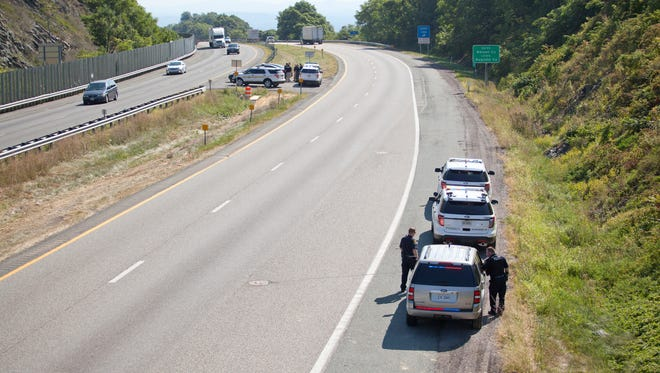 Law enforcement officers gather along I-64 in Afton in search of the shooter who killed two WDBJ7 journalists during a live interview at Smith Mountain Lake on Wednesday, Aug.