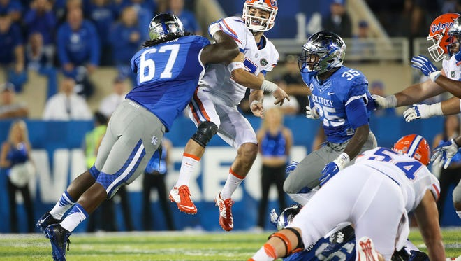 Florida quarterback Will Grier is hit by Kentucky defensive tackle Cory Johnson, left, after throwing a pass during the first half of an NCAA college football game, Saturday, Sept. 19, 2015, in Lexington, Ky. (AP Photo/David Stephenson)