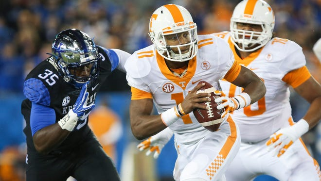 Tennessee quarterback Joshua Dobbs scrambles in front of Kentucky defensive end Denzil Ware during the first half of an NCAA college football game Saturday, Oct. 31, 2015, in Lexington, Ky. (AP Photo/David Stephenson)