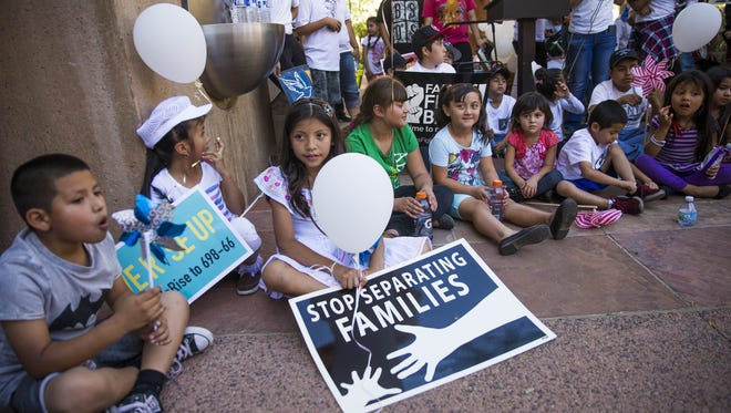 Kids sit in front of Phoenix City Hall on April 30, 2017. Promise Arizona held a march and rally against deportation efforts and to support immigrant communities.