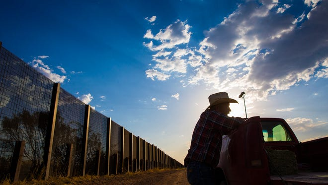 May 5, 2017; Naco, Ariz, USA; Rancher John Ladd leans on his truck on his ranch, which borders with Mexico (behind him). He has been frustrated for years over the illegal border crossers and drug smugglers that cut through his ranch. The 16,000 acre calf/cow operation has been in the Ladd family for 121 years. Mandatory Credit: Michael Chow/The Arizona Republic via USA TODAY NETWORK