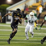 University of Southern Mississippi's Justice Hayes (7) runs the ball through the North Texas defense at the game in M.M. Roberts Stadium on Saturday.