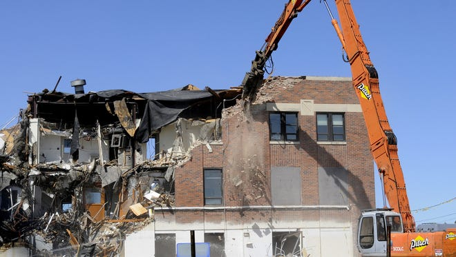 Crews raze buildings at the former Michigan State Police headquarters site  in East Lansing in May of 2012.  Greg DeRuiter/LSJ