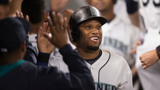 Seattle Mariners' Robinson Cano is congratulated by teammates after scoring during the fifth inning of a baseball game against the Oakland Athletics, Tuesday, Aug. 25, 2015, in Seattle.