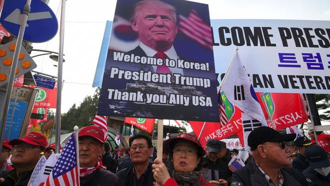 """A photo taken on Nov. 8, 2017, shows demonstrators holding a placard showing a picture of President Trump as they wait for his appearance outside the National Cemetery in Seoul. US President Donald Trump's notoriously threatening rhetoric towards nuclear-armed North Korea -- which has drawn comparisons with Richard Nixon's """"madman theory"""" of diplomacy -- may deserve some credit for bringing Pyongyang to talks, analysts have said."""