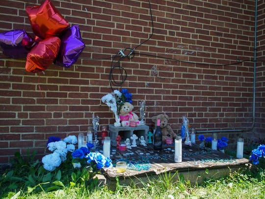 A memorial rests against the home where Morgan Dixon, 26, who was shot while driving Wednesday evening on North Claymont Street in Wilmington, crashed in the Riverside neighborhood.