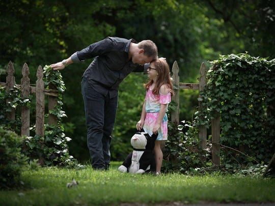 Matt Hearn talks to his daughter Josephine, 9, with stuffed dog Buster while wearing Lee dark denim jeans; an Express charcoal gray cotton long-sleeve sports shirt; and brown leather stitched cowboy boots by Ariat.