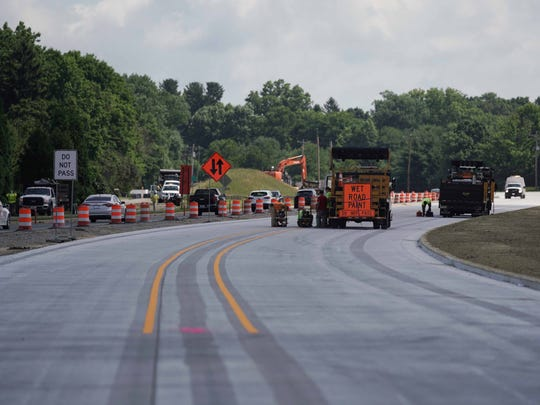 """Construction workers paint the new lane lines along the Del. 141 Starting around 8 p.m. Friday, traffic on Del. 141 will move to a new """"contraflow pattern"""" on the newly reconstructed northbound lanes of the roadway."""