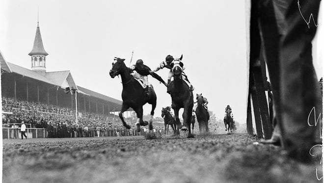 This photograph, showing the furious stretch battle between jockeys Don Meade on Brokers Tip (right) and Herb Fisher on Head Play,art the finish of the 1933 Kentucky Derby, was almost an accident. Courier-Journal photographer Wallace Lowery lay on the ground, stuck his camera under the rail and shot. This picture is the result. It is probably the most widely circulated picture in the history of the Derby.  By Wallace Lowery, The Courier-Journal.  May 1933.