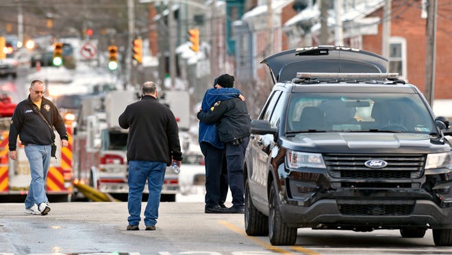 York City Fire deputy chief Chad Deardorff, second from right, greets a York City Police officer at the scene of a partial building collapse at the old Weaver Organ and Piano building Thursday, March 22, 2018, the day after a fire destroyed much of the building in York. York Mayor Michael Helfrich confirmed that two firefighters, Ivan Flanscha and Zachary Anthony, died and that two others, assistant chief Greg Altland and firefighter Erik Swanson, are recovering from their injuries.