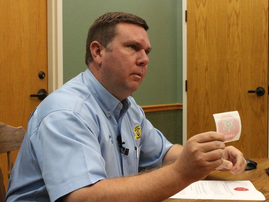 Grant Parish Sheriff Steve McCain holds a sticker S.T.O.P.S.,
