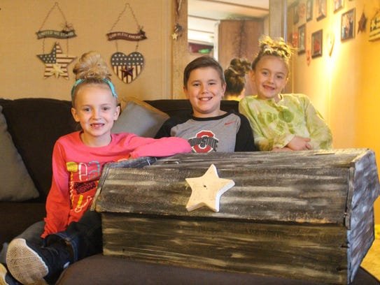 From left to right, Lilly, Owen and Leigha Gates, ages 8, 10 and 7 respectively, pose with the memory box where they put letters to their father, who relapsed last year and died of an overdose.