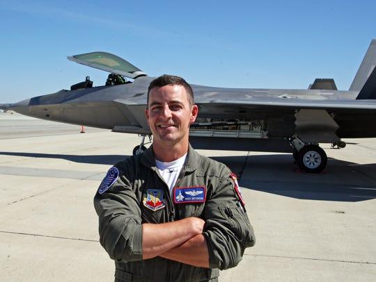 "Major Dan ""Rock"" Dickinson stands before the F-22 Raptor"