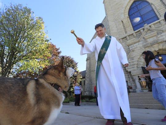 Deacon Paul Umentum sprinkles holy water on, Keisha,