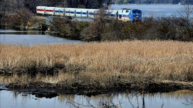 A Metro-North commuter train from New York City travels north toward the Beacon train station in this photo taken Monday morning looking southwest across marshland near Denning's Point. The Hudson River is in the background.