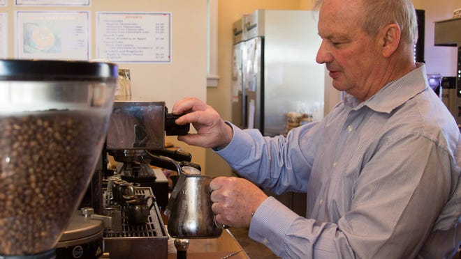 Phillip Jewell, owner of Blue Hat Coffee, steams milk for a latte in his coffee shop on Friday.
