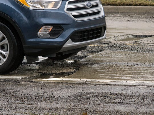 Cars weave through the potholes, but it's hard to avoid