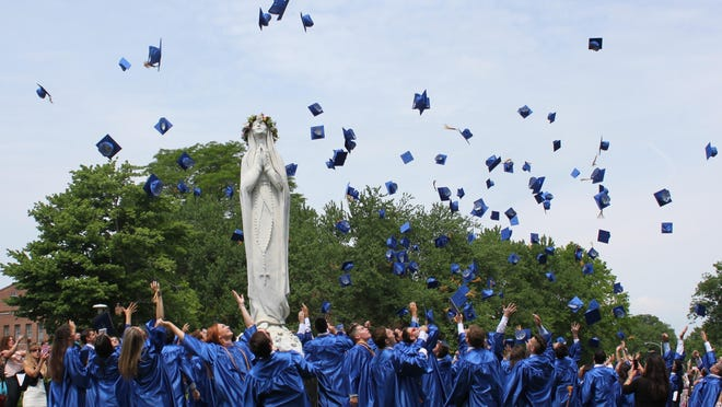 Graduates at Our Lady of Lourdes High School toss their mortarboards after commencement Saturday.