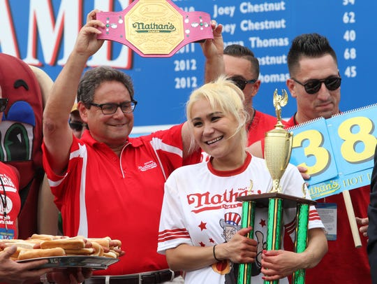 Miki Sudo holds her trophy and smiles after winning