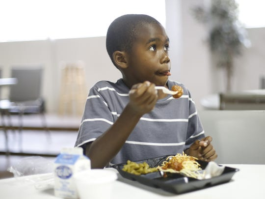 Kylen Welch eats a meal of spaghetti and meatballs  delivered by Bethel AME Church's 2015 summer feeding program.