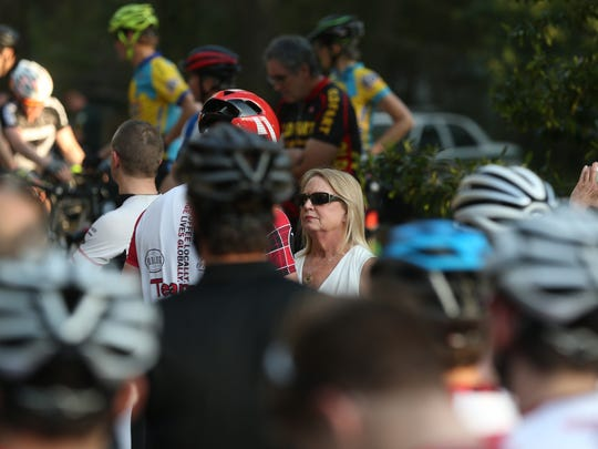 Christine Reker, in glasses, widow of Stephen Reker who died Tuesday evening after being hit by a car while riding his bike, is surrounded by fellow cyclists Wednesday after a memorial ride in his honor.