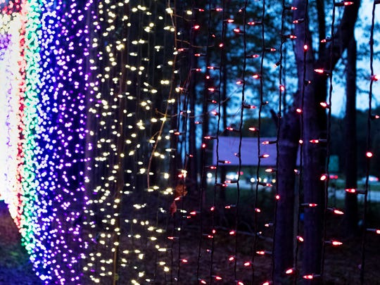 Traffic on I-20 is visible from a tunnel made of lights at Candy Cane Lane Drive-Thru Christmas Light Park in Calhoun.