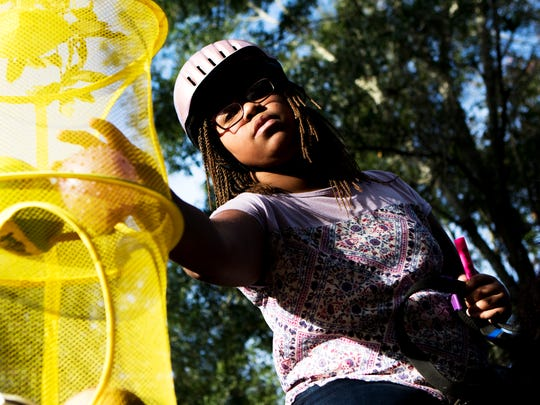 Naima Davis, 11, reaches for a plastic ball hanging