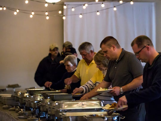 Customers serve themselves during the fish fry at the RiverEdge Golf Course  in Marshfield, Wis., Friday, March 30, 2018.