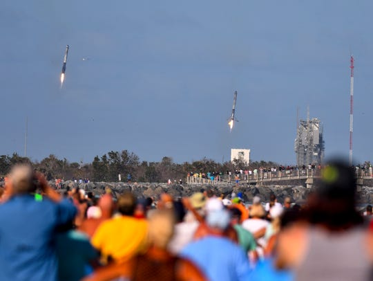 Crowds in Cape Canaveral watch  two of the three boosters