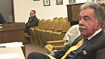 Millville Municipal Prosecutor Michael R. Mazzoni (seated, foreground) is shown at a special City Commission meeting held March 31 to consider firing him. Mazzoni has now announced he will resign.