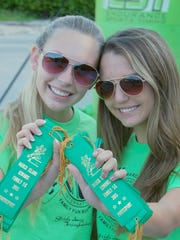 Caitlyn Schmidt, left, and Cassidy Carlson - doing voluntary hours on behalf of the Marco Island Academy's Key Club - show off ribbons that were later presented to finishers.