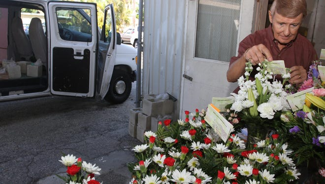 Cliff Shell checks his orders before loading up the van to make deliveries for Ruth Messmer Florist on Monday morning. The local florist has been forced to raise prices for its deliveries because of the recent uptick in gas prices.