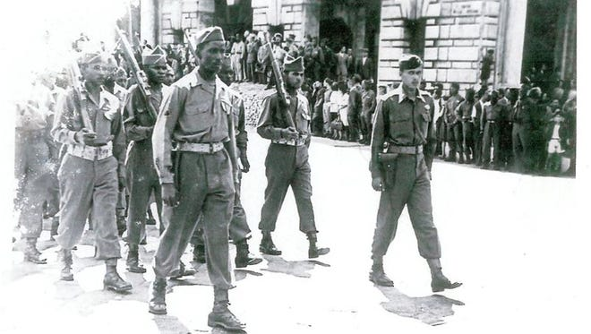 James H. Gilliam Sr. (far right) leads a platoon of Buffalo Soldiers on a march into Genoa, Italy, in June 1945, as the 92nd Infantry Division returned what was believed to be the ashes of explorer Christopher Columbus. The Army is looking for relatives of unaccounted for soldiers from this Division.