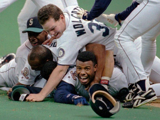 FILE - In this Oct. 8, 1995, file photo, Seattle Mariners' Ken Griffey Jr. smiles from beneath a pile of teammates who mobbed him after he scored the winning run in the bottom of the 11th inning of a baseball game against the New York Yankees, in Seattle. The Seattle Mariners are the only baseball franchise never to advance to the Fall Classic. Baseball has never been played in Seattle beyond Oct. 22. The Mariners have three times been to the American League Championship Series, and all three times were sent home before there could ever be a Game 7.(AP Photo/Elaine Thompson, File)
