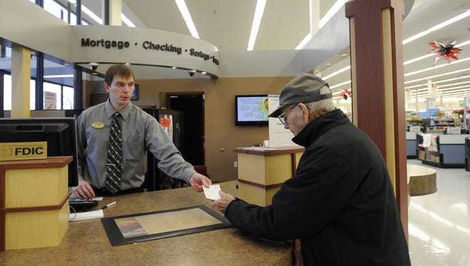 Josh Lawson, Home Federal personal banker supervisor, helps Norman Meyer at Hy-Vee on Marion Road and 26th Street in Sioux Falls, S.D., Thursday, Dec. 20, 2012. (Emily Spartz / Argus Leader)