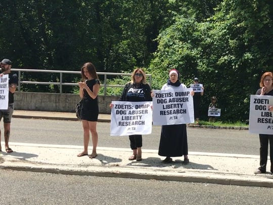 PETA members stage a protest outside of the global