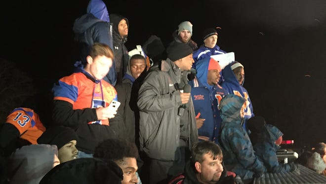 Millville Thunderbolts, coaches and players, jam together atop a city fire truck Monday night during a bonfire and fireworks celebration of the team's victory in the South Jersey Group 5 football championship game. Center in a black knit cap is Coach Dennis Thomas