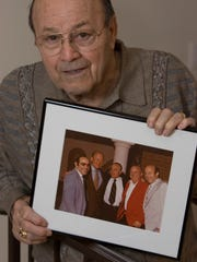 Joe Garagiola holds a photo in 2006 taken with President
