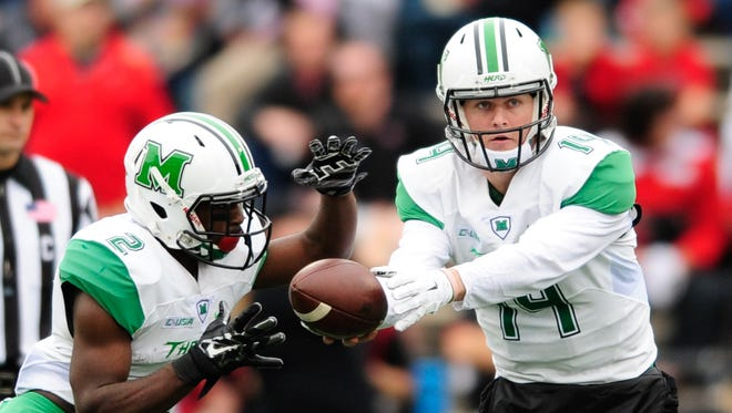 Marshall Thundering Herd quarterback Chase Litton hands off to Hyleck Foster.