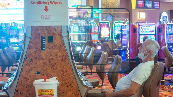 File - David Potoma, of Philadelphia, plays slots near a sanitizing area after the re-opening of Parx Casino in Bensalem in June.