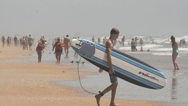 Beachgoers enjoy the beach in Surf City, N.C. Sunday Aug. 2, 2020.