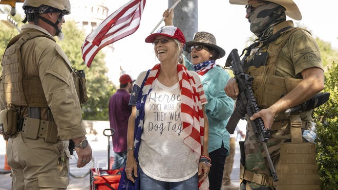 Kim Stevenson, middle, of Tarpley, and two men carrying rifles attend a rally to protest the results of the presidential election at the Texas Capitol on Nov. 21.