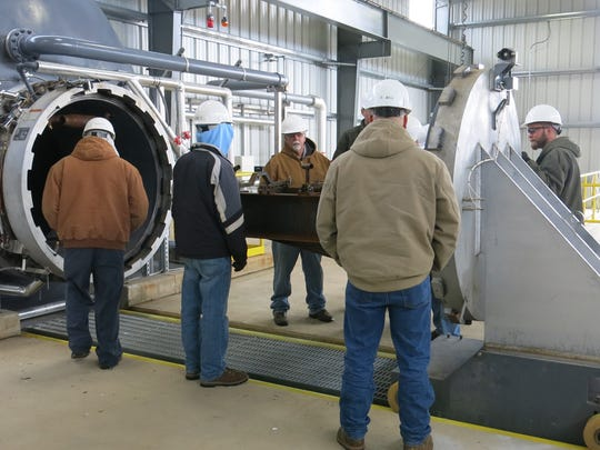 Letterkenny Munitions Center employees inspect the rocket motor clamping fixture and loading trolley into the Thermal Treatment Chamber autoclave at the Ammonium Perchlorate Rocket Motor Disposal Facility.